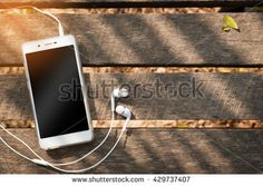 Smartphone with blank area on touch screen and in ear headphone on rustic wood table at outdoor area in morning time with high contrast natural lighting