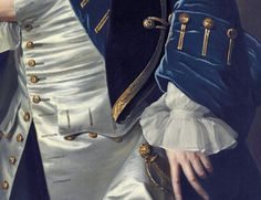 Blue velvet frockcoat with wide upturned cuff and three gold buttons, ivory silk waistcoat with gold button detail matching frockcoat, shirt with ruffle at wrist, ornate sword hilt to left hip,  black velvet tricorne with gold braid trim under arm. Right hand slotted in waistcoat - the pose for an 18thC gentleman. Detail from Portrait of a gentleman, 1749, Thomas Hudson.