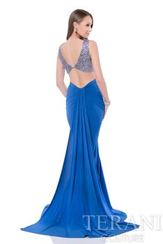 Two piece prom dress with boatneck beaded crop top and open v back. This prom gown is paired with a ruched jersey column skirt and back drape overlay.