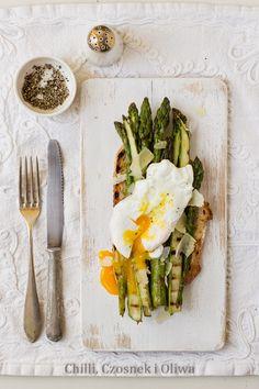 Grillowane szparagi podane na kromce chleba z parmezanem i jajkiem w koszulce - pyszna propozycja na śniadanie.