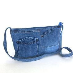 This small messenger bag is constructed from recycled blue denim pant. It has two of original open pockets on the front side. I lined it with dark blue fabric.It features one inside pocket ,and top zipper closure. This messenger bag is not very tall,and can accompany you on many different adventures.  Measurements: width:13.5 height: 8 depth: 1.5 single strap: 45  Machine washable and dry able
