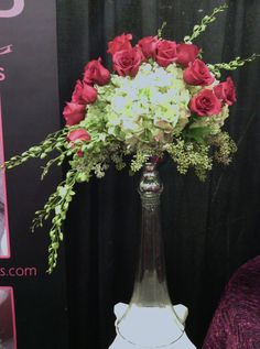 Tall voluptuous wedding centerpiece of antique green hydrangeas with raspberry pink roses and green orchid sprays collared with seeded eucalyptus in tall silver & glass pedastal
