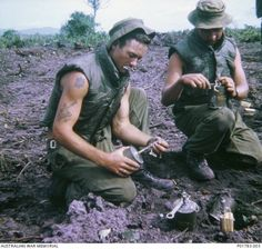 """Tough men doing a tough job! Laying mines!   Corporal Trent Grall (left) and Lance Corporal Barry O'Brien, both of the Assault Pioneer Platoon, Support Company, the 7th Battalion, The Royal Australian Regiment (7RAR), priming M16 anti-personnel (""""jumping jack"""") mines. They are laying the mines in the 11 kilometre-long minefield that the 1st Australian Task Force (ATF) was constructing from Dat Do to the coast.   South Vietnam - May, 1967"""