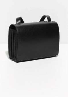 16305a3e863 A sleek leather bag accented with contrasting pleat details on sides and a  long adjustable shoulder