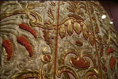 Vienna Schatzkammer house, back of a cope or pluviale, a  clerical cape that goes over the rest of the vestments.  The embroidery is a combination of raise gold and silver work and beads (coral). embroidery.
