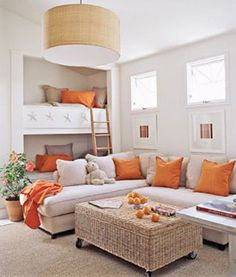 The accented color in this room is a red-orange. The walls, are an off white, while the neutral pillows are tan. There is a light tan sofa along with an earthy simple hanging light.