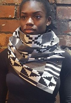This infinity style neck wrap with front press stud fastenings in gunmetal black can be worn in a variety of ways. Fashioned from black and white African Kente print block wax cotton fabric, it offers a real and wearable statement for style conscious generation bold enough to rock African print. This item is from the Urbanized 'Ethnic' Range. This range is characterised by its use of African inspired printed fabrics in vibrant colours and urban designs. The inspiration behind this range