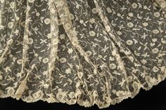 A lace cape worn by Norma Shearer as the title character in her Academy Award nominated role in Marie Antoinette (MGM, 1938). The lace has a floral and foliate pattern and is embellished with hand sewn artificial pearls and scattered celluloid sequins of varying sizes with scalloped edges.