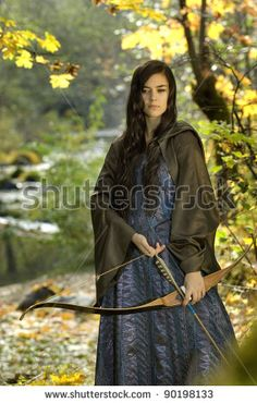 Beautiful Young Female Ranger with bow in Woodlands - stock photo