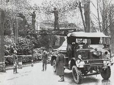 Soldiers balancing on a crane to suspend camouflage over the road adjacent to Field Marshal Montgomery's headquarters in Broadwater Down c1940/1941.