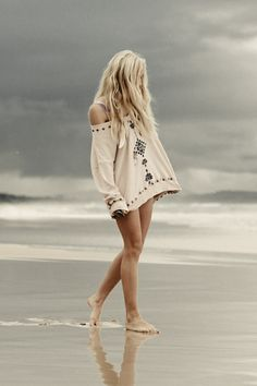 The girlfriend walking along a beach. The weather in the background is dull however this highlights what the boyfriend sees, the beauty of his girlfriend