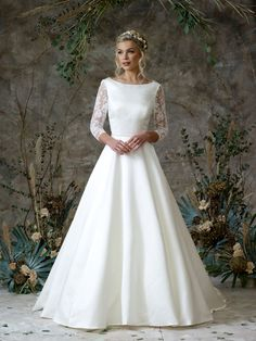 This sophisticated satin dress features an elegant boat neck, a princess skirt (with pockets!) and gorgeous lace sleeves. The lace spreads to the back where a delicate tie creates a stunning keyhole effect. Older Bride, Bridal Separates, Ethereal Beauty, Designer Wedding Gowns, Satin Gown, Gorgeous Wedding Dress, Princess Wedding, Lace Sleeves, Pockets
