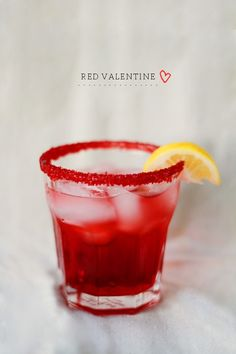 Red Valentine Cocktail 1.5 ounce of Patron silver tequila, 1 ounce Organic brand lemonade, splash of Rose's, Red grenadine syrup, red sugar for rim, lemon wedge, ice