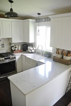 Quartz countertop, whit cabinets, white backsplash. Dark wood floor, nickel faucet with farmhouse sink