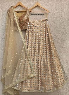 Nude gold mirror work lehenga with gold border teamed with an antique gold sequins blouse with hints of pink and turquoiseFlaunted with a lovely gold dupatta with an intricate gold border and gold buttisComposition: NetAll pro. Dress Indian Style, Indian Dresses, Indian Outfits, Mirror Work Lehenga, Mirror Work Saree Blouse, Indian Lehenga, Net Lehenga, Lehenga Choli, Bridal Lehenga Collection