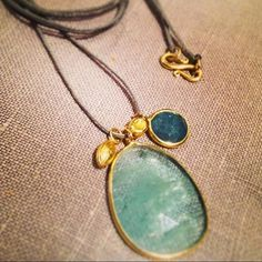 Ocean tones of Aquamarine and Tourmaline amulet pendants with small gold seeds #PippaSmall #PippaSmallJewellery #EthicalJewellery #EthicallyMade #AmuletCollection #GoldNecklace #GoldJewellery #Aquamarine #Tourmaline