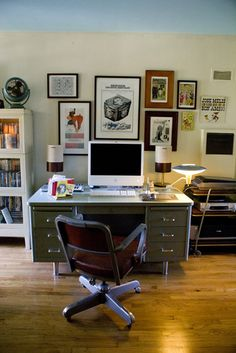 favorite elements: vintage desk and chair, the white walls, and the collage of mismatched frames as a backdrop