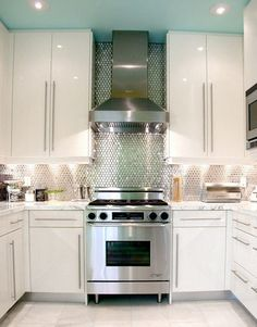 turquoise painted ceiling, silver backsplash, white kitchen, stainless steel stove