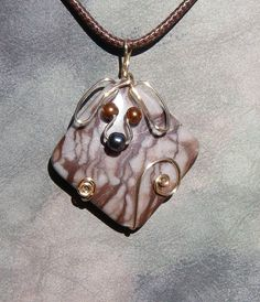"This unique handmade pendant is a cute gold tone wire dog with glass eyes and a hematite nose on a beautiful brown striped jasper stone. The stone is approximately 1.5"" x 1.5"". The pendant is hung on a brown cord with silver tone clasp."