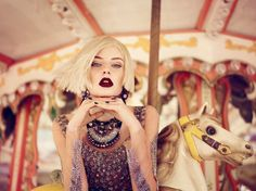 I like this picture because the subtle movement of the model's hair ties in the background of the merry go round; Photographer: Luis Monteiro