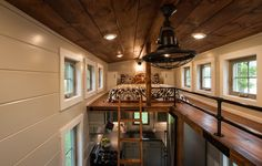 The Retreat: a 416 sq ft tiny house from Timbercraft Tiny Homes. The home has two loft bedrooms, a living room with a fireplace, a full kitchen, and a bathroom.