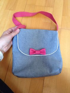 Petite besace pour l'école, pour Capucine. En jean avec du passepoil argenté et un petit nœud en simili cuir rose.