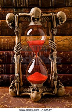 Skeleton hour glass with old antique books - Stock Image
