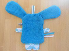 Doudou plat lapin bleu blanc • Tissu poils mi-long bleu pour le devant du corps • Tissu poilu bleu pour lenvers du corps et lenvers des oreilles • Tissu blanc triangles bleus - bleu bulles bleues • Pupille - nez : polaire noire • Taille des oreilles aux pattes environ : 27 cm • Taille que
