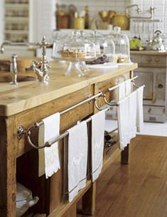 Vintage French towel racks are mounted on an antique English baker's table base with a new sycamore top and prep sink - designed and remodeled by owner Susan Dossetter and architect #Andrew #Skurman.