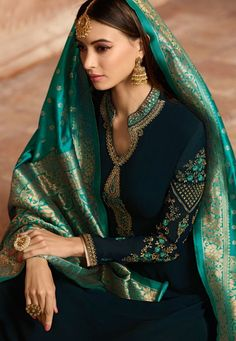 Navy Blue Embroidered Satin Churidar Suit shows combination of embossed zari and thread detailed embroidery on heavy georgette satin top paired with customised churidar/pants satin bottom and linin. Pakistani Bridal Dresses, Pakistani Dress Design, Indian Dresses, Indian Outfits, Bridal Lehenga, Churidar Suits, Salwar Kameez, Chikankari Suits, Indian Attire