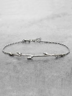 A beautiful earthen branch bracelet with tiny buds is the perfect adornment for your boho earth goddess. Handcrafted in lightly antiqued Sterling Silver, and finished with a tiny jewel on the end of t