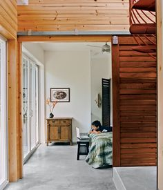Sliding slatted doors separate the asymmetrical downstairs spaces.  Photo by Linny Morris.