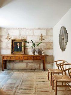 Recibidor con paredes de piedra y consola antigua