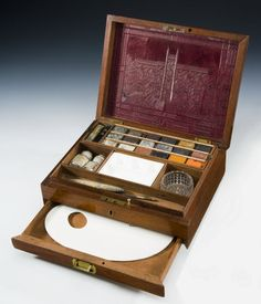 A mid 19th century mahogany artists box complete with watercolour tablets, mixing dishes, porcelain palette and other objects. The inside of the lid has an embossed leather panel showing a building and the name J. Newman, Manufactory.