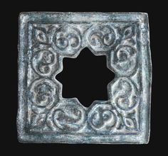 A FINE RAQQA TURQUOISE GLAZED POTTERY TILE, SYRIA, LATE 12TH/EARLY 13TH CENTURY moulded and decorated with a rich vivid opalescent turquoise alkaline glaze with a central aperture in the form of an eight-pointed star enclosed by high relief split-palmette scrolls and a trilobed palmette in each corner within raised line borders
