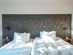 A DIY stenciled bedroom accent wall in dark gray and metallic gold using the Flock of Cranes from Cutting Edge Stencils. http://www.cuttingedgestencils.com/bird-flock-wall-stencil-pattern.html
