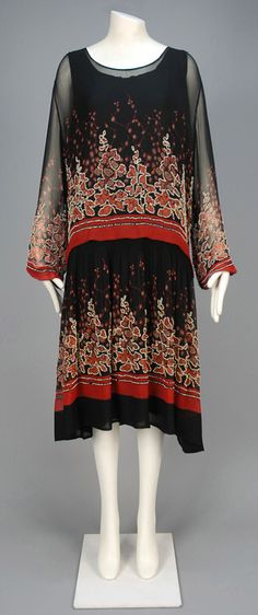 PRINTED and BEADED CHIFFON DAY DRESS, 1920s. Black chiffon with abstract floral and graduated bands in red, rust and taupe decorated with white beads having long sleeve gathered into narrow cuff, dropped waist and gathered skirt, crepe underdress.