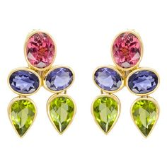 Peggy Stephaich Guinness Multicolored Gemstone Drop Earrings  Pink tourmaline, iolite and peridot drop earrings, the gemstones bezel-set in 18k yellow gold. Two oval-shaped pink tourmaline weighing 9.50 total carats and two pear-shaped peridot weighing 17.82 total carats. Designed by Peggy Stephaich Guinness.        Price: $8,000