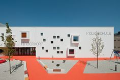 a collaboration between austrian practice MAGK and illiz architektur, 'childcare center' is an elementary school and kindergarten in maria enzersdorf, austria. geometric windows and framed boxes projecting from the white surface create a dynamic envelope which contrasts the boldly colored pavement which encompass the building. the pixelated facade integrates playful colors to highlight special spaces for children including play areas and window box seats.