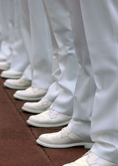 U.S. Naval Academy Midshipmen stand at parade rest during a Brigade summer whites uniform inspection.