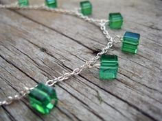 When Irish eyes are smiling handmade Emerald Green Glass Necklace and Earrings. Add some sparkle to your outfit with this dainty jewelry set. The emerald green cube charm necklace is dainty and delicate with matching dangle emerald green cube earrings. A silver plated chain is used on this set that would be perfect for the holidays, St. Patrick's Day or a wedding accessory.