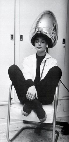 Audrey Hepburn chilling in a salon while smoking a french cigarette and getting her hair done