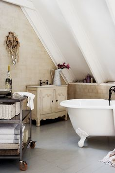 Beautiful bathrom - love the sloped ceiling, the soothing color and especially the industrial cart for towels/supplies.