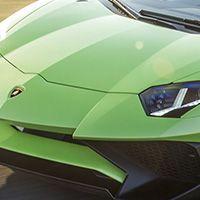Front shot of a green Lamborghini Aventador SV Coupé racing on a track.