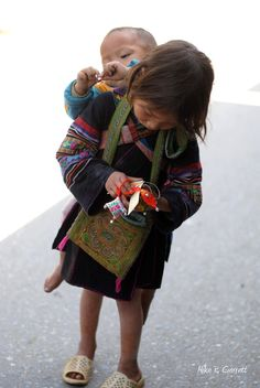 "Early Responsibility - ""A little girl carrying her baby brother is walking down the Sapa Market ,Sapa Vietnam. While taking her responsibility to take care of the little brother, she is enjoying her own toy.""  National Geographic Photo Contest"