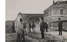 As you can see, this was gentlemenly attire in Boole's day! Here are men with chimney pot hats at Cork's Custom House 1861