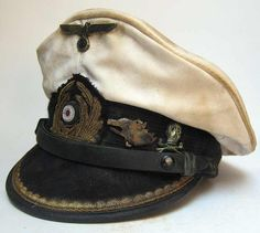 Reproduction German U-Boat Submarine Captains Peaked cap with 70+ years of ageing and some worn and tarnished areas as worn by the Captain of U-566 - Hans Hornkohl.  It has two badges: The 'Suckling She Wolf' & the Brunswick tradition badge. The Wolf is the emblem of the U-Boat but there is no information as to why Hornkohl wore the tradition badge. www.warhats.com