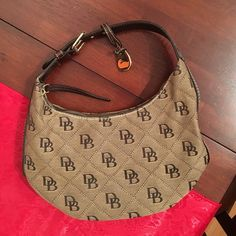 Dooney & Bourke small handbag Authentic Dooney & Bourke small stretch slouch bag. Used fairly, in great condition! Red lining. Dooney & Bourke Bags Mini Bags