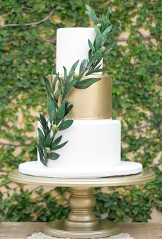 Brides.com: 29 Glam Metallic Wedding Cakes. A three-tiered white and gold wedding cake with greenery accents, from The Sugar Suite.