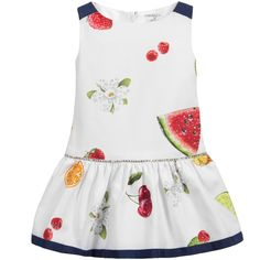White, sleeveless dress by Monnalisa, with an all-over tropical fruits print. The dropped waist is embellished with a band of sparkling diamantés and the gathered skirt below is edged with navy blue grosgrain ribbon. Made of cotton piqué, there is a concealed zip fastener at the back of this lovely dress.